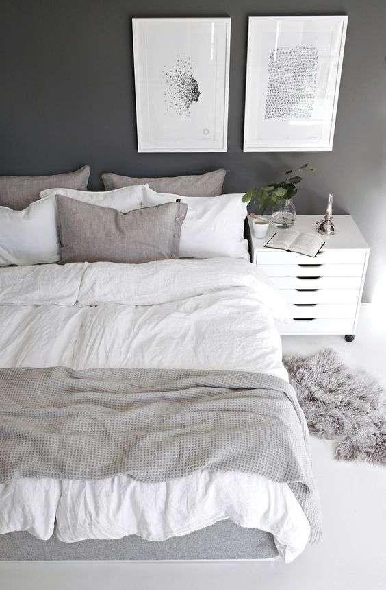 Cette chambre propose des tons de gris et de blanc ainsi que deux tableaux minimalistes
