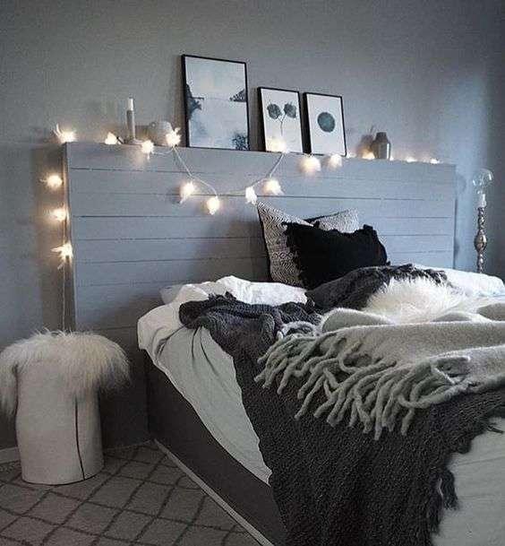 Chambre grise avec tête de lit éclairée et des cadres