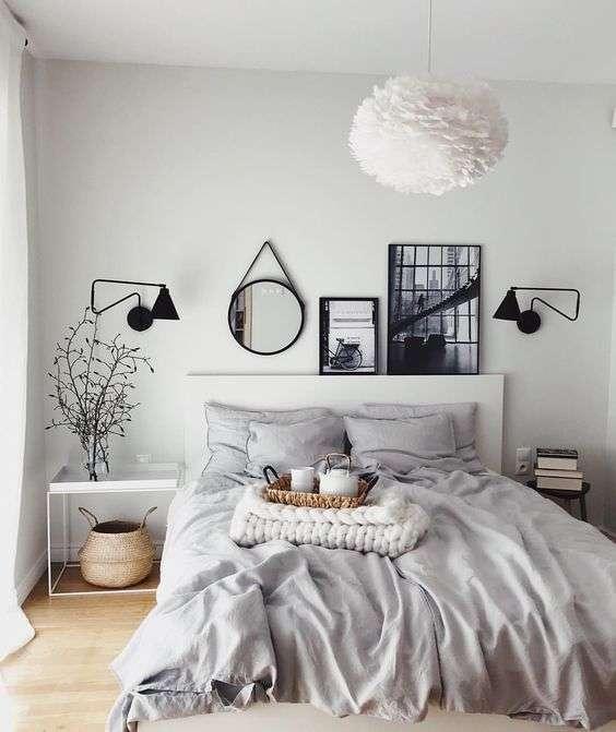 Chambre grise très claire avec cadres, miroirs et plantes pour un contraste accru