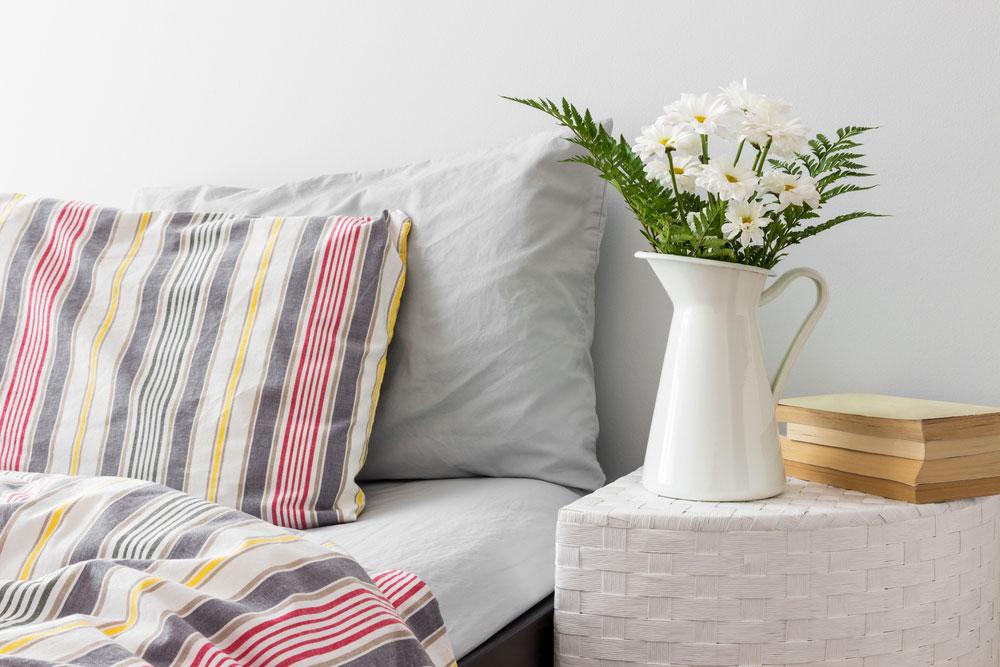 Chambre avec des fleurs sur la table de chevet