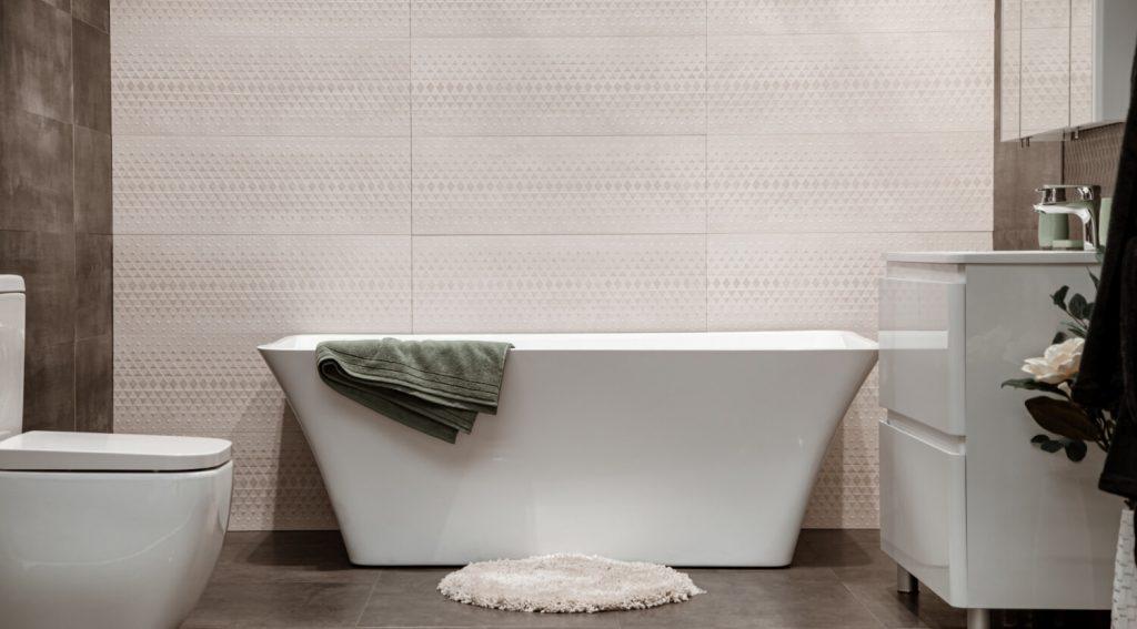 Baignoire devant mur en carrelage dans la salle de bain